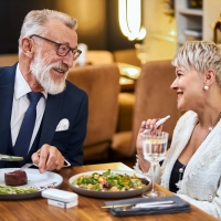 Senior modern couple taking a meal in restaurant using IQOS, electronic cigarette